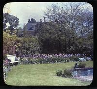 Tulips, pond, and bench in an unidentified garden with view of house in background