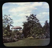 Woman seated at umbrella table in gardens of Alice Lea Spruance at The Patch