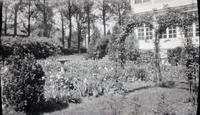 Flowers at rear of house with archway and birdbath in gardens of Alice Lea Spruance at The Patch