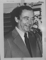 William G. McGowan holding a radio headset up to his ear