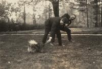 William Fisher and unidentified man playing with dog at the home of Fred Fisher