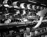 Sizing or putting a protective coating on nylon yarn in DuPont plant at Seaford, Delaware