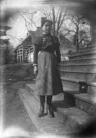 Unidentified girl with watch on wooden steps