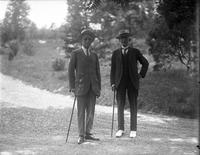 Two older men wearing boater hats with canes