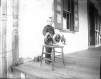 "Roy Benge, Sr., as a child on porch with a one-cylinder gas ""Hit or Miss Engine"""