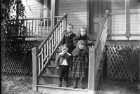 Four unidentified children on stairs to a porch