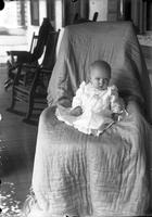 Baby posed on chair on porch