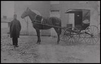 Man next to horse-drawn carriage in front of carriage shed on Blacksmith Hill at Hagley