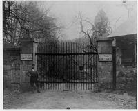 Man standing in front of closed Blacksmith Shop gate entrance to Hagley Yard