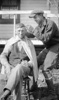 Man seated outdoors getting a haircut