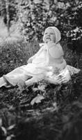 Elizabeth (Biz) Schoonover as a baby seated on grass wearing hat and sweater