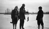 Cortlandt Schoonover and other boys ice fishing on frozen pond