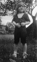 Elizabeth (Biz) Schoonover as a child outdoors wearing romper and hat
