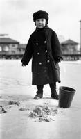 Cortlandt Schoonover as young child playing on the beach during winter