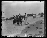 Cape May, two women and a man walking on the beach