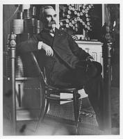 Pierre A. Gentieu seated at E.I. du Pont de Nemours & Company exhibit at 1899 Sportsmen's Exposition