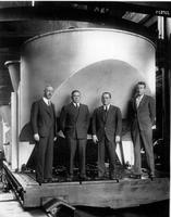 Captain Clyde S. McDowell, Guenther H. Froebel, Rein Kroon, and unidentified man posing with south crossbeam for Hale Telescope yoke mount at South Philadelphia Works