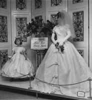 Departmental display at Macy's Herald Square location (New York, N.Y.) promoting Miss America bridal gown of Ban-Lon lace and flower girl dress