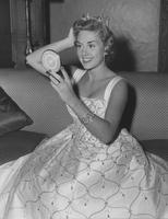 Marian McKnight, Miss America 1957 seated with compact