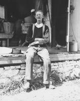 John McVey seated on edge of porch