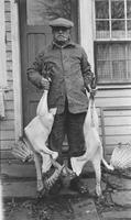 Howard Ellsworth Seal, Sr. holding two plucked turkeys at back door
