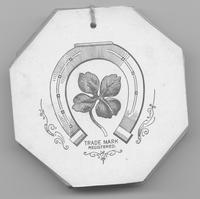 Back of Gobelin Art Drapery Co. textile tag depicting a horseshoe surrounding a four-leaf clover