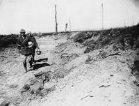 Two soldiers carrying German helmets during World War I
