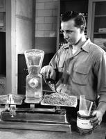 Chemist in a DuPont Company laboratory measures out a pound of pure silicon