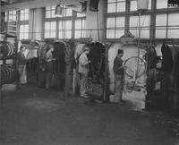 Workers at painting station in wheel factory