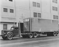 Truck with trailer in front of factory