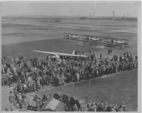 Crowd at airfield surrounding single-engine plane