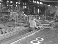 Man working at cutting machine, rail brace