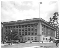 Exterior of Chamber of Commerce building with people and cars