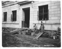Exterior construction of Chamber of Commerce building with workers