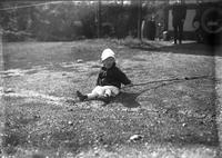 Norman Mancill as a young child sitting on lawn with stick