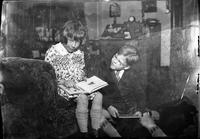 Tom Marshall, Jr. and his cousin Eleanor Marshall reading books in the living room