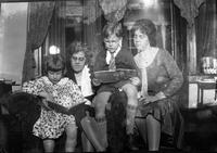 Tom Marshall, Jr., his mother, his cousin Eleanor, and unidentified woman reading books in the living room