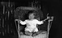 Thomas Marshall, Jr., as a toddler seated in wicker chair