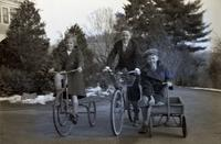 Tom Marshall, Jr., with two other children outside during winter with cycles and a wagon