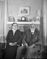 Unidentified older couple in front of fireplace