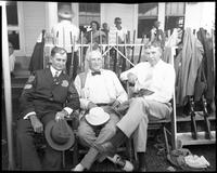 Three men seated in front of gun rack during 1940 trapshooting event