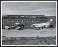 Two planes in front of Atlantic Aviation building