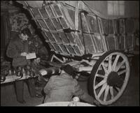Three men inspecting Conestoga powder wagon in barn