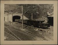 Main Line haulage locomotive and trip of loaded mine cars coming through the concrete portal of a mine