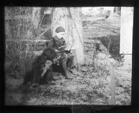 Boy reading under a tree with a dog