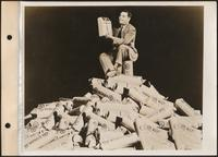Man holding a wallbox sitting on a mountain of rolls of nickels