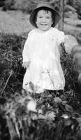 Cortlandt Schoonover as young child standing outdoors wearing sun hat