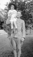 Cortlandt Schoonover as young child being held on shoulders by a man in military uniform
