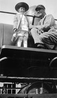 Cortlandt Schoonover as young child holding oil can with train engineer on locomotive