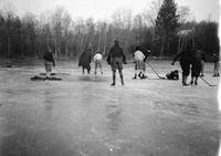 Cortlandt Schoonover and other young people playing ice hockey on frozen pond